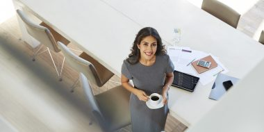 Portrait smiling businesswoman drinking coffee in conference room